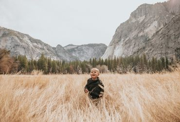 Child in Field With Mountain Backdrop